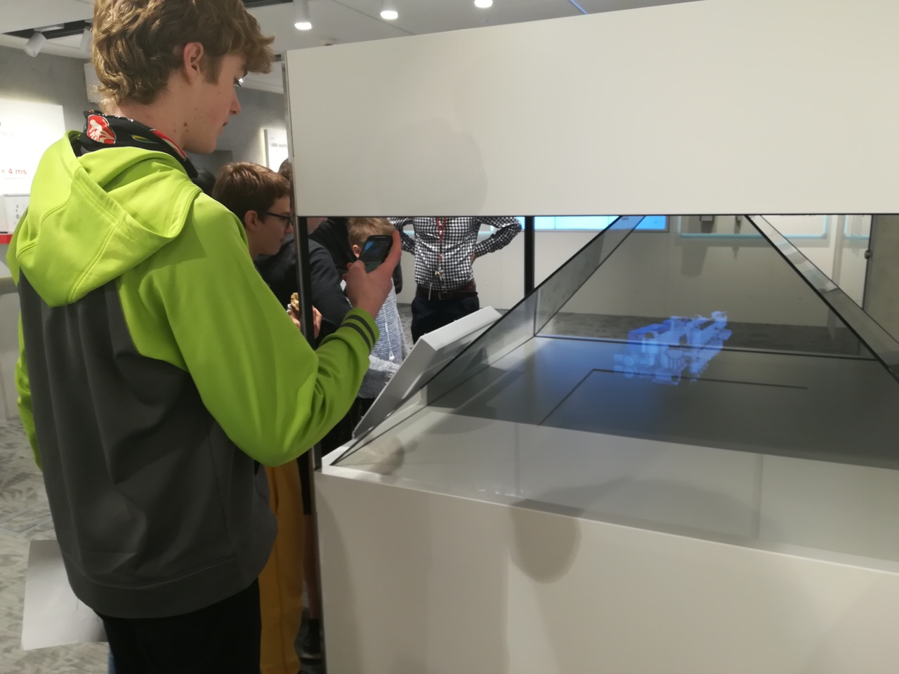 A student photographs the hologram at ABB Robotics